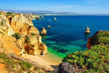 FototapetaBeautiful sandy beach Praia do Camilo with wooden walkway near Lagos. Algarve region, Portugal