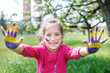 Cheerful child with hands in a paint. Concept of education, education, childhood, lifestyle.