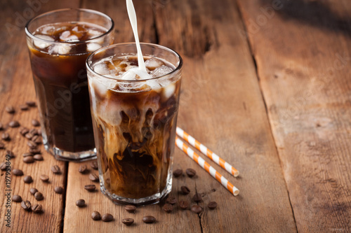 Ice coffee in a tall glass with cream poured over and coffee beans on a old rustic wooden table Canvas Print