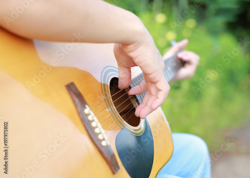 Fotografia Close-up male hand playing on acoustic guitar against nature background
