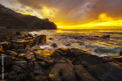 Fotografia  Dynamic sunset over the ocean, rocky beach in the Canary Islands
