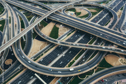 fototapeta na drzwi i meble Aerial view of big highway interchange with traffic in Dubai, UAE, at day. Scenic cityscape. Colorful transportation, communications and driving background.