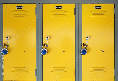 Fototapeta Yellow school lockers with locks - Three locker doors of three yellow lockers in the hallway of a school, each with number plates, and a stainless steel combination lock with a blue knob on the face