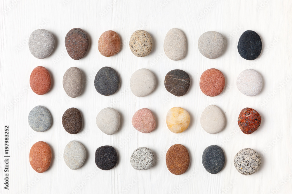 Fototapety, obrazy: Pattern of natural multicolored pebbles on white wooden background.