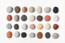 Pattern Of Natural Multicolored Pebbles On White Wooden Background.