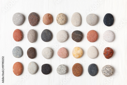 Fotografía Pattern of natural multicolored pebbles on white wooden background