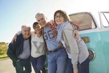 Group of senior friends standing by camper van