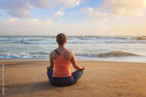 Woman doing yoga Lotus pose oudoors at beach