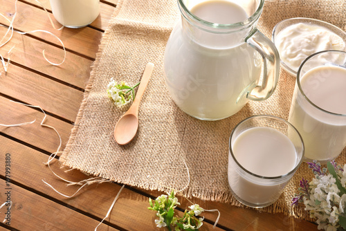 Glass of milk on wooden table outdoor in nature