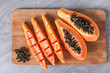 canvas print picture - Papaya fruit cut in slices on wooden background