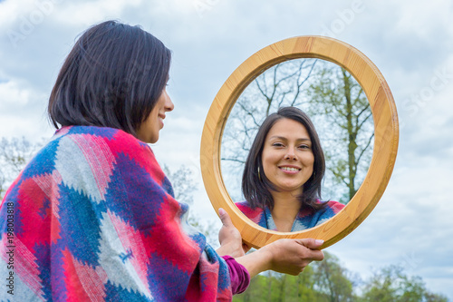 Woman looking at mirror outside in nature