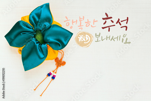 Fotografía  'Happy Chuseok & Hangawi, Translation of Korean Text : Happy Korean Thanksgiving Day' calligraphy and Korean traditional bag & knot background of white ramie fabric