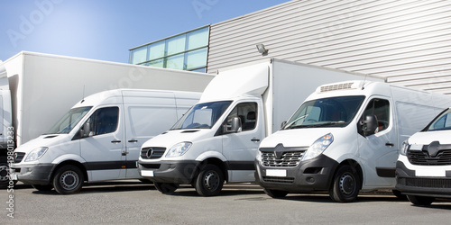 delivery white vans in service van trucks and cars in front of the entrance of a warehouse distribution logistic society - fototapety na wymiar