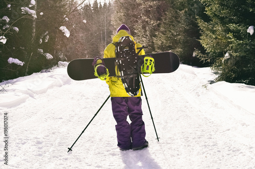 Photo Back view of walking man with snowboard and snowshoes going on backcountry tour