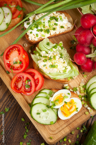 Summer sandwiches ingredients - cucumber, radish, tomato, mozzarella and eggs, white wood background, top view