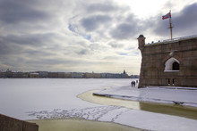 Panoramic View Of St. Petersburg And Neva River Under Ice In Winter From Peter And Paul Fortress, Nevsky Gate, Naryshkin Bastion And Flag Tower. Footprints From Shoes On Snow, St. Petersburg, Russia