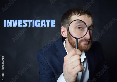Foto  A businessman shows an inscription:INVESTIGATE