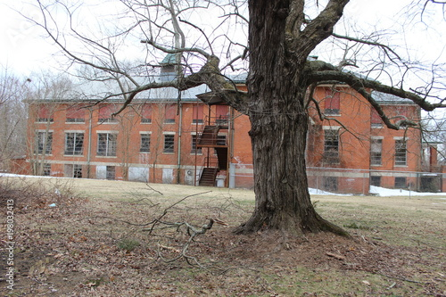 Photo Old abandoned and boarded up brick asylum hospital building