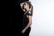 Young female model in black dress on the contrast black and white background. Fashion art studio photo