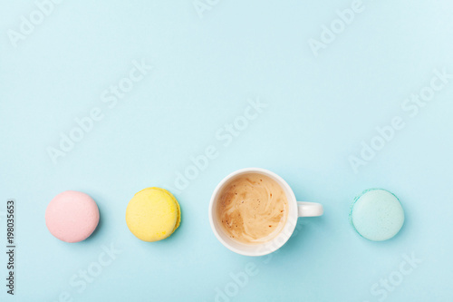 Poster Macarons Fresh coffee and colorful macaron on pastel blue background top view. Cozy morning breakfast. Fashion flat lay style. Sweet macaroons.