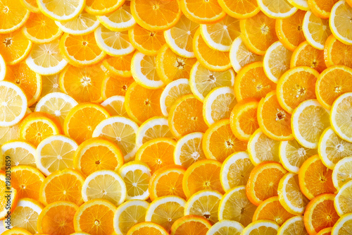 Photo Stands Slices of fruit Abstract background of sliced orange and lemon. Top view.