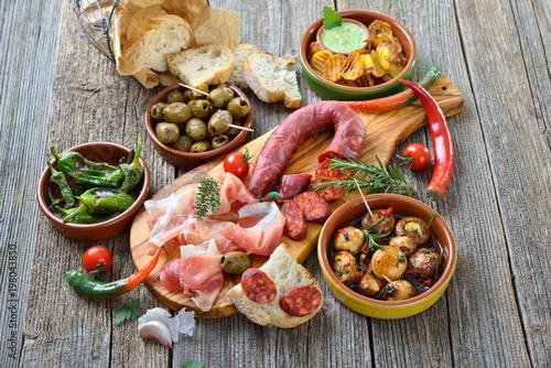 Foto auf AluDibond Bar Iberische Spezialitäten: Spanische Chorizo, Serrano-Schinken und weitere Tapas – Typical Iberian bar food: Spicy chorizo sausage, Serrano ham and other mixed tapas