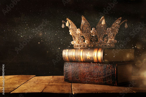 low key image of beautiful queen/king crown on old books. fantasy medieval period. Selective focus.