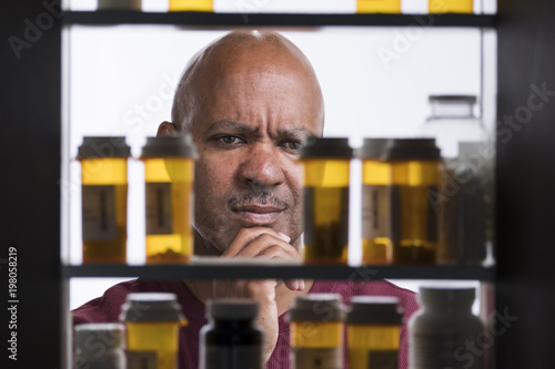 Fotografie, Obraz  Man overwhelmed with bottles of pills in his medicine cabinet