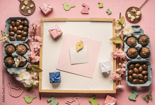 Fototapety, obrazy: Easter composition, greeting card,, around lined with various chocolate eggs, decorations and toys on a pink background, top view, space for text flat lay