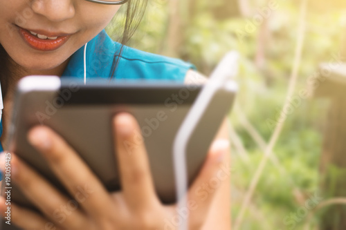 Fotografie, Obraz  Asian women are using tablets in the garden.