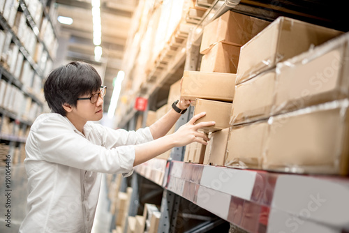 Foto Young Asian man picking paper box from shelf in warehouse, shopping warehousing