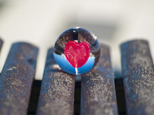 A Crystal Ball In A Wooden Bench, Reflecting One Red Candy Heart Shape