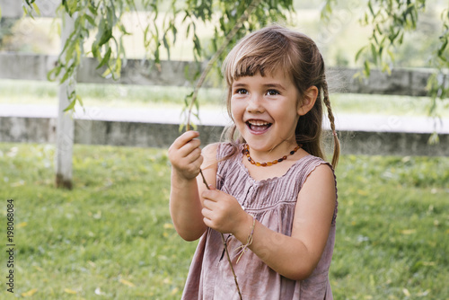Cute happy girl playing with stick in park