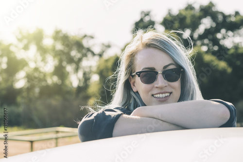 Smiling woman in sunglasses leaning on car