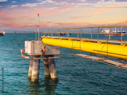 Canvas Print Workers are repairing and painting bollard for mooring  on sea at industrial por