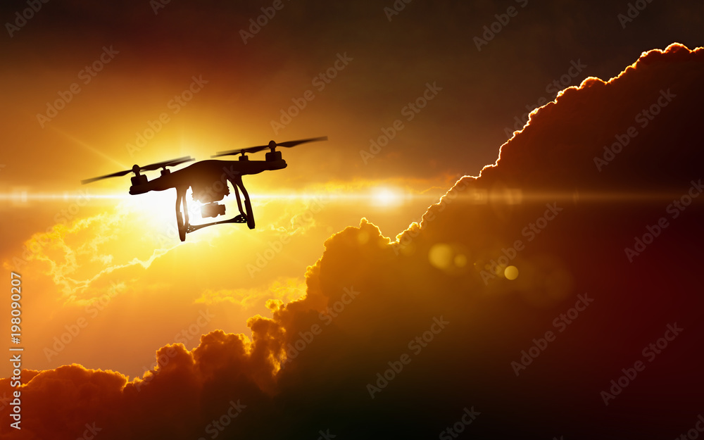 Fototapeta Silhouette of flying drone in glowing red sunset sky
