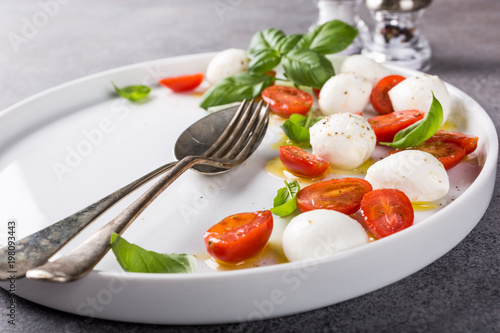 Recess Fitting Appetizer White plate of healthy classic delicious caprese salad with ripe tomatoes and mozzarella cheese with fresh basil leaves on gray concrete background with space for text. Italian food.