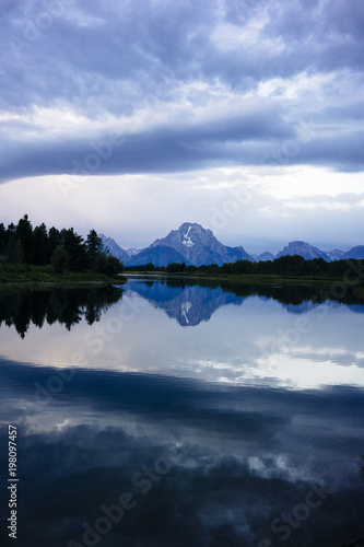 Tuinposter Bergen Scenic view of lake and mountain against cloudy sky at Grand Teton National Park