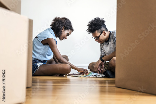 Smiling young man and woman choosing from color swatches while sitting on floor by boxes at new home