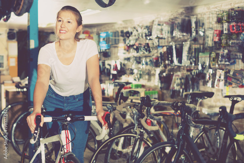 Deurstickers Fiets Portrait of girl who is standing with bicycle in store.