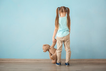 Lonely Little Girl With Teddy Bear Near Color Wall. Autism Concept