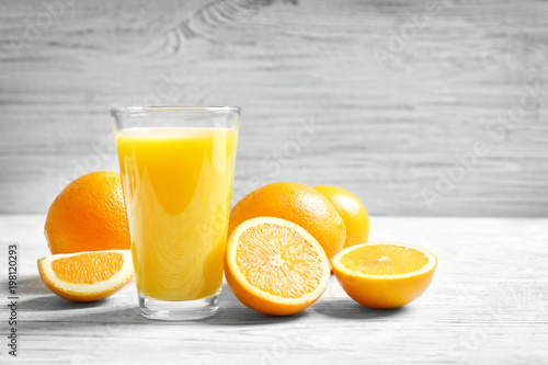 Glass of orange juice and fresh fruits on table