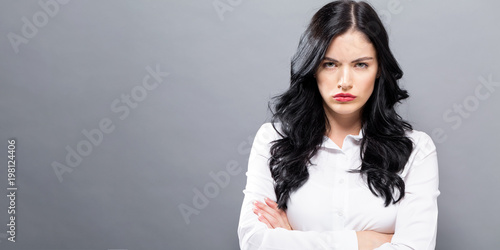 Fotografering  Unhappy young woman on a solid background