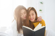 Beautiful young asian women LGBT lesbian happy couple sitting on bed reading book together near window in bedroom at home. LGBT lesbian couple together indoors concept. Spending nice time at home.