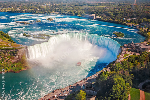 Fototapeta Aerial top landscape view of Niagara Falls and tour boat in water between US and Canada