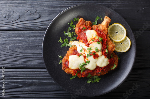 Veal Milanesa Napolitana with mozzarella cheese and tomato sauce close-up on a plate. horizontal top view