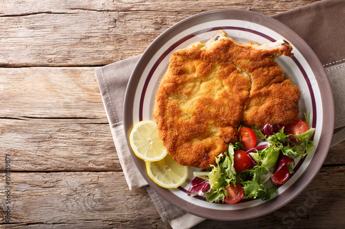 veal Milanese with lemon and fresh salad of tomatoes and lettuce close-up Canvas Print