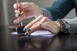 Woman make calligraphy writings, make art on a paper using pen brush and sign pen. Adult, old hands of a calligrapher woman. Lifestyle image of a design process