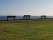 Three park benches diagonally looking out to the ocean