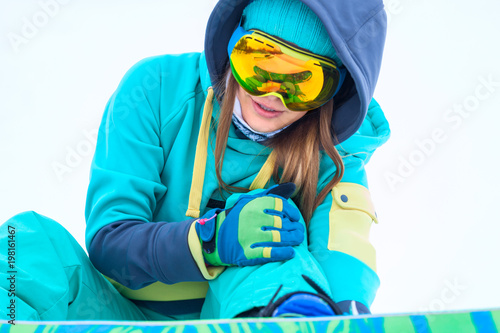 Young snowboarder holding her injured leg.